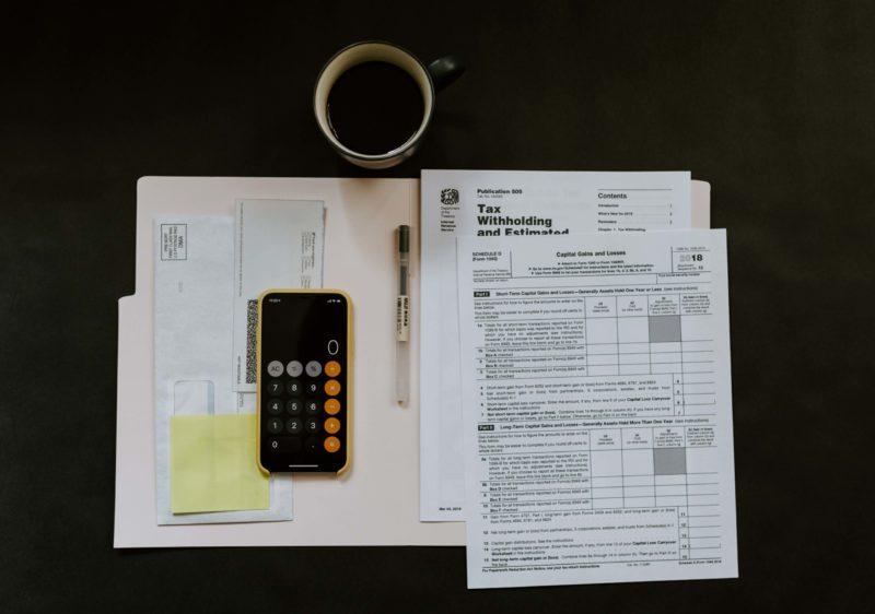 Mesa com papéis de contas e celular